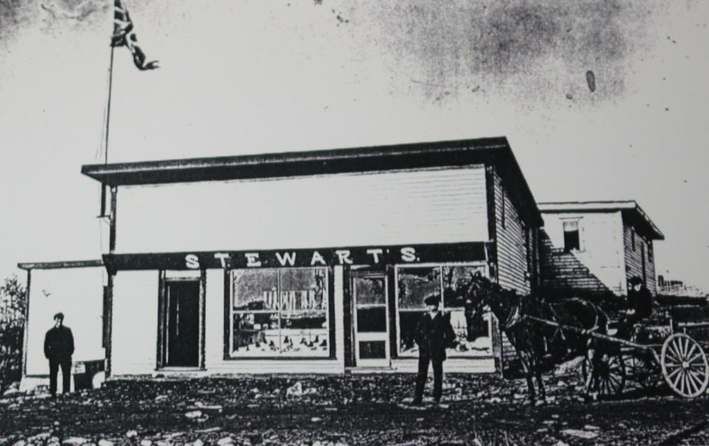 Photographie d'archives en noir et blanc. Vue de la rue. Le bâtiment principal a deux portes d'entrée et deux grandes fenêtres. Un Union Jack flotte à gauche au-dessus du bâtiment. Deux hommes sont debout dehors et un autre homme conduit une charrette à cheval.