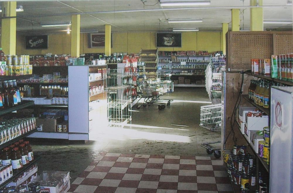 Photographie couleur.  Plusieurs chariots sont alignés dans le couloir, des boîtes de conserve et des bouteilles garnissent les étagères et le sol à l'avant à droite est quadrillé rouge et blanc, alors qu'il est beige à gauche et à l'arrière de la photo.