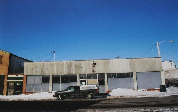 Photographie couleur.  Vue extérieure du magasin Stewart's. Le bâtiment a été construit dans les années 1950, suite à un incendie sur la rue Main de Windsor. Un camion est garé devant le bâtiment.