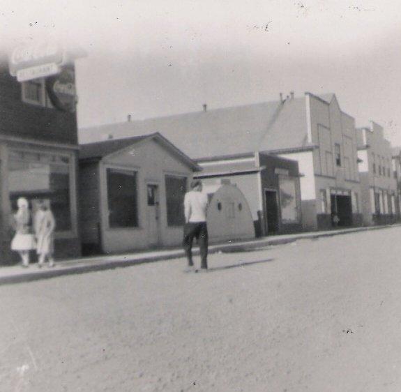 Photographie noir et blanc. Vue de la rue. Vue de la rue Main en direction de l'est. Le bâtiment métallique semi-circulaire (3 e depuis la gauche) est la remorque à frites Stroud's.