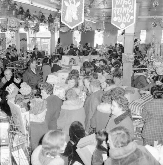 Photographie d'archives en noir et blanc. Plus de 70 personnes en manteaux d'hiver et chapeaux font la file chez Cohen. Des décorations de Noël et des bannières pendent du plafond.