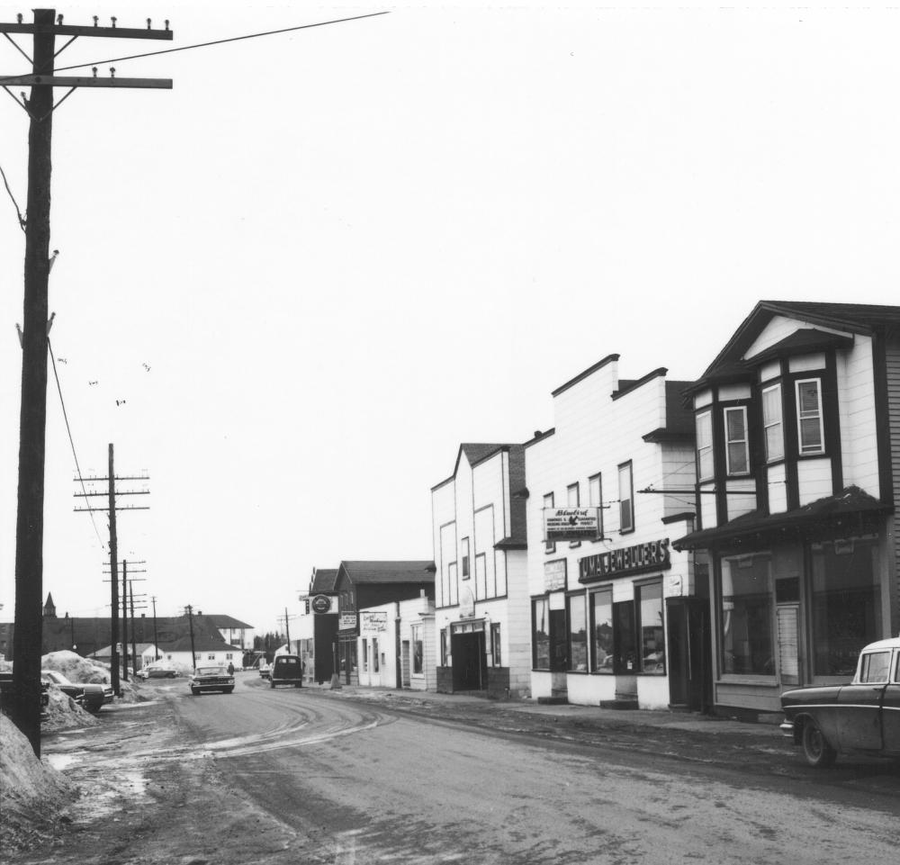 Photographie d'archives en noir et blanc. Vue de la rue. Du côté droit de la rue, plusieurs commerces de la rue Main. Le côté gauche de la rue présente un alignement de poteaux. On aperçoit l'église St Joseph à l'arrière-plan, sur la gauche.
