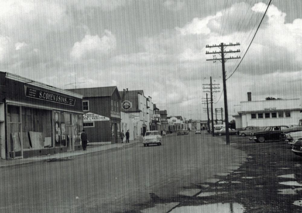 Photographie d'archives en noir et blanc. Vue de la rue. À gauche de la photo, des commerces de la rue Main. À droite, des poteaux téléphoniques et la gare ferroviaire. Il y a quatre voitures dans la rue et plusieurs piétons sur le trottoir, à gauche de la photo.