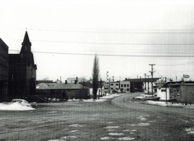 Photographie d'archives en noir et blanc. Vue de la rue. Vue vers le nord en direction de la rue Main de Windsor depuis l'église St Joseph, qui se trouve à gauche de la photo. À droite, on voit le bâtiment de Canadian Tire et, au centre, le panneau de signalisation des voies de chemin de fer.