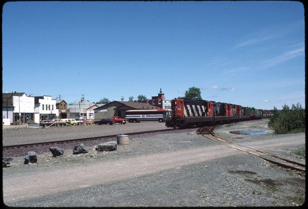 Photographie couleur. Vue en direction de la rue Main depuis l'autre côté des voies de chemin de fer. À droite, on voit le train CN et au centre, la gare ferroviaire.
