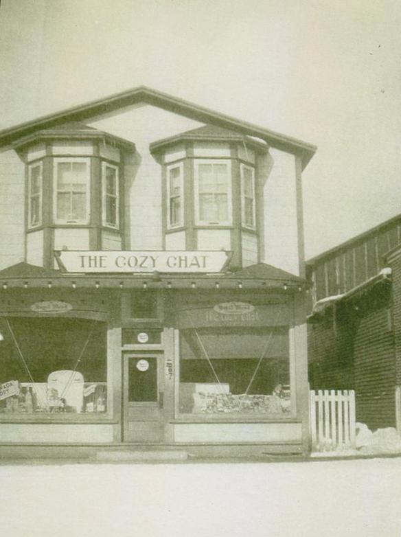 Photographie noir et blanc. Vue extérieure du Cozy Chat. Deux fenêtres en baie au deuxième étage.