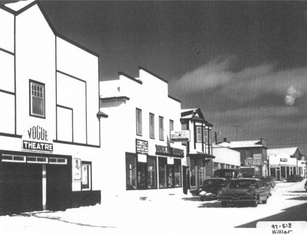 Photographie d'archives en noir et blanc. Vue de la rue. Au centre de la photo et à droite du cinéma Vogue se trouvent le magasin de chaussures Connolly's et la bijouterie Tuma.