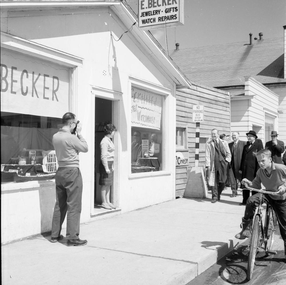 Photographie d'archives en noir et blanc. Vue de la rue. Vue extérieure de la bijouterie d'E. Becker. Un homme à gauche de la photo prend une photo, une femme se tient sur le seuil du magasin, un groupe de six hommes en costume marche en direction du magasin et un garçon passe à vélo.