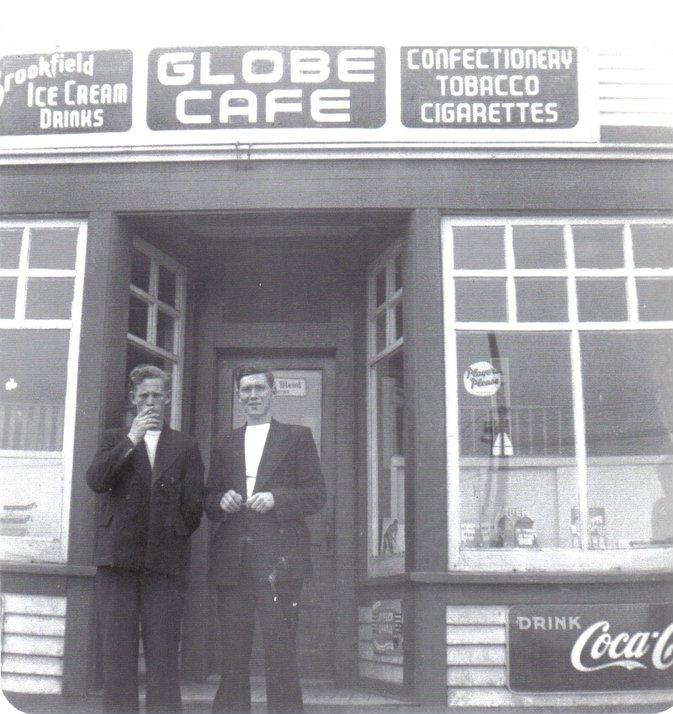 Photographie noir et blanc. Deux hommes debout sur les marches du Café Globe, entre les deux fenêtres en baie. Textes des panneaux situés au sommet de l'immeuble, de gauche à droite : Brookfield ICE CREAM DRINKS, GLOBE CAFE, et CONFECTIONERY, TOBACCO, et CIGARETTES (CRÈMES GLACÉES Brookfield, BOISSONS, CAFÉ GLOBE, et CONFISERIE, TABAC, et CIGARETTES). Texte du panneau en bas à droite : DRINK Coca-Cola (BUVEZ Coca-Cola).