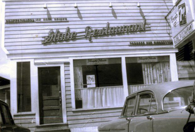 Photographie noir et blanc. Deux voitures sont garées devant le restaurant Globe. Textes des panneaux situés en dessus de la porte, de gauche à droite : CONFECTIONERY ICE COOL DRINKS, Globe Restaurant, et TOBACCO AND CIGARETTES (CONFISERIE BOISSONS GLACÉES, Restaurant Globe, et TABAC ET CIGARETTES). Un écriteau indiquant « Players Please » (« Players » s'il vous plaît) est accroché dans les deux fenêtres.