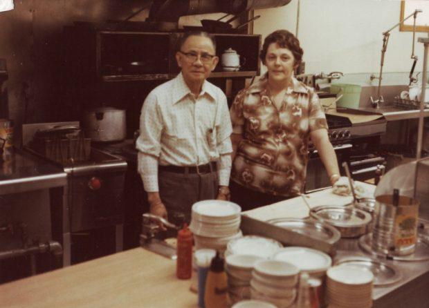 Photographie couleur.  Intérieur de la cuisine du restaurant Globe. On distingue un four derrière l'homme et la femme qui sont au centre de la photo.