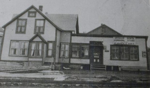 Photographie d'archives en noir et blanc. Vue de la rue. Vue extérieure du magasin American Gents Furnishing Store S. Cohen & Fils de la rue Main.