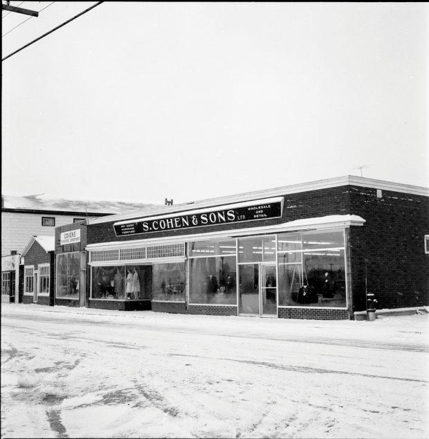 Photographie d'archives en noir et blanc. Vue de la rue. Vue des magasins S. Cohen & Sons et Cohen's Furniture Department, en direction de l'ouest de la rue Main. Au-dessus du magasin on peut lire : DRY GOODS; HARDWARE; FURNITURE; S. COHEN & SONS LTD.; WHOLESALE AND RETAIL (MERCERIE ; QUINCAILLERIE ; MEUBLES ; S. COHEN & FILS LTD ; VENTE EN GROS ET AU DÉTAIL). Des mannequins homme et femme sont visibles dans les vitrines du magasin.