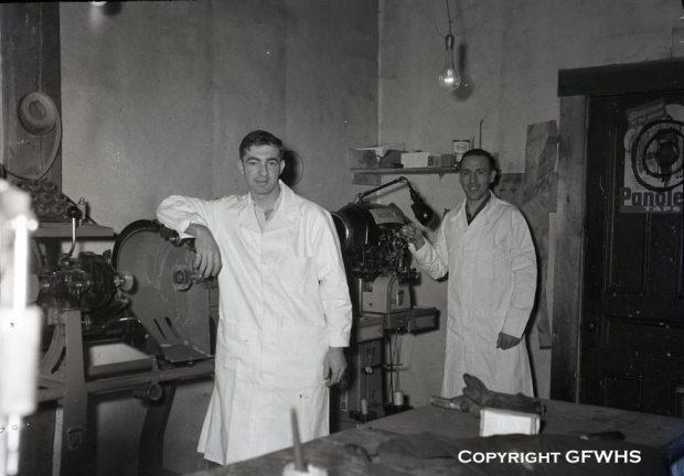 Photographie d'archives en noir et blanc. Deux hommes en blouses de laboratoire sont debout chez le cordonnier Hermann Münch.