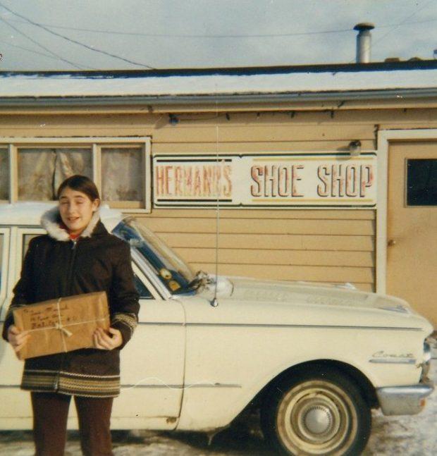 Photographie couleur. Vue de la rue. Une fillette portant un manteau d'hiver et tenant un paquet se tient devant une voiture blanche, devant la boutique du cordonnier Hermann's Shoe Shop.
