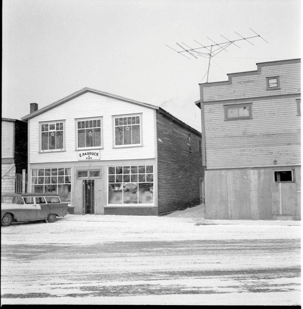 Photographie d'archives en noir et blanc. Vue de la rue. Vue extérieur du magasin E. Paddock & Fils pendant la saison de Noël. On peut voir des guirlandes décoratives et des étoiles aux fenêtres, ainsi que des jouets exposés dans les vitrines du bas.