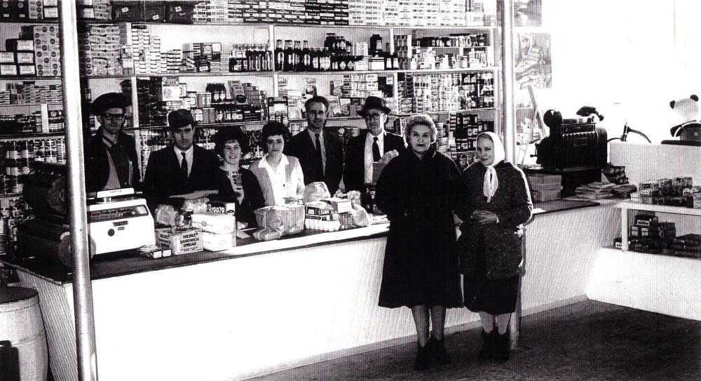Photographie d'archives en noir et blanc. Quatre hommes et deux femmes se tiennent derrière la caisse et le comptoir, et deux femmes en manteau devant le comptoir. Les étagères situées derrière la caisse sont remplies d'emballages, de boîtes de conserve et de bouteilles de produits.