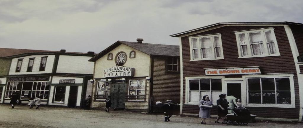 Photographie d'archives couleur. Vue de la rue Main de Windsor en direction de l'ouest. On voit le Brown Derby, le cinéma King Edward, les magasins A. Peckford et S. Cohen & Fils et le café Purity. Kirk Pomeroy porte un balai en bouleau, Daisy Bennett porte un manteau bleu-gris et Mme Pomeroy pousse une poussette.