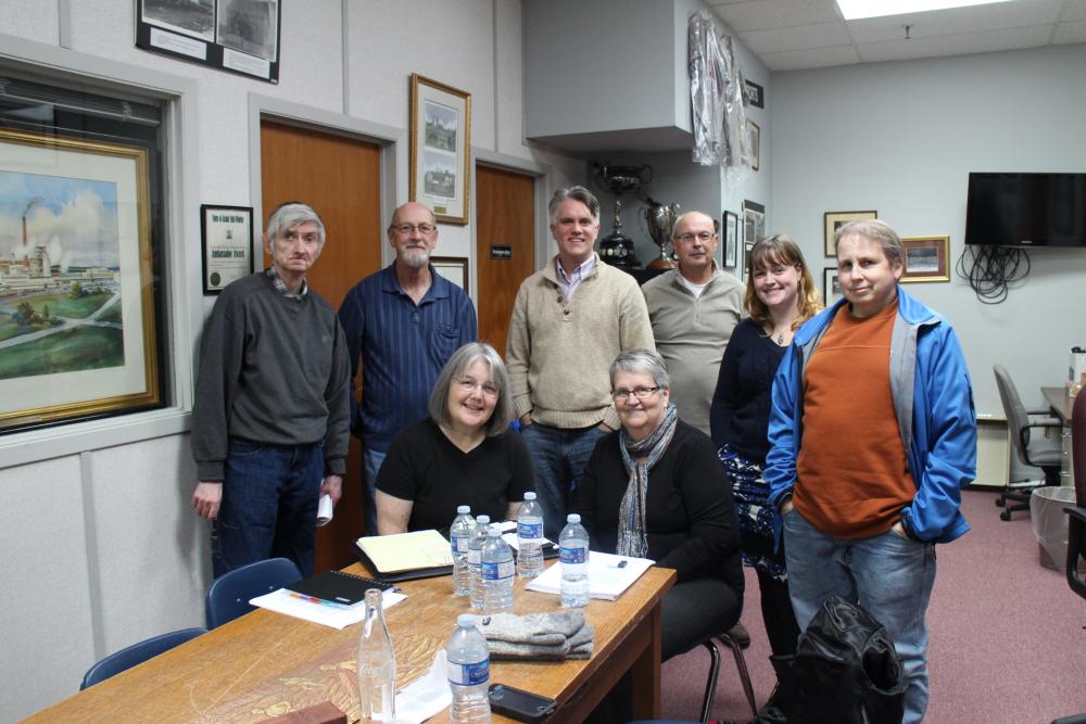 Photographie couleur. Debout de gauche à droite se trouvent quatre hommes, une femme et un autre homme. Assises à table, deux femmes