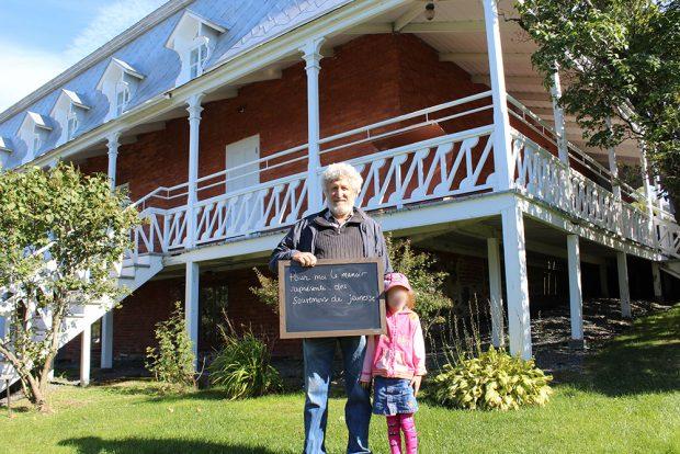 Photo couleur. Un homme accompagné d'une jeune fille tient un tableau dans les mains. Une maison de briques est en arrière plan.