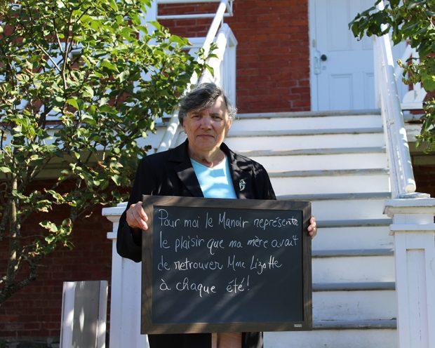 Photo couleur. Portrait d'une femme qui tient un tableau noir dans les mains. À l'arrière, on distingue un escalier menant à une galerie.