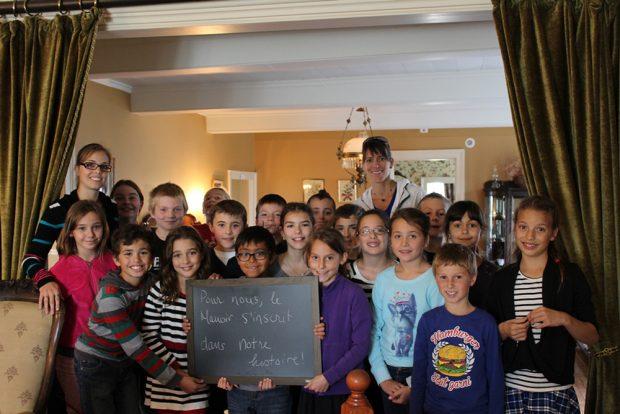 Photo couleur. Classe d'une vingtaine d'étudiants de niveau primaire prennent la pose. l'un d'eux tient un tableau noir sur lequel il est écrit ce que le manoir représente pour leur classe.
