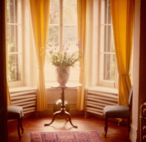 Photo couleur. Hall d'entrée du Manoir avec un bouquet de fleurs dans la bay window.