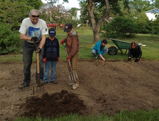 Photo couleur. Au premier plan, un homme montre à deux garçons à remuer la terre du potager. À l'arrière-plan, une femme et une jeune fille enlève les roches du potager.