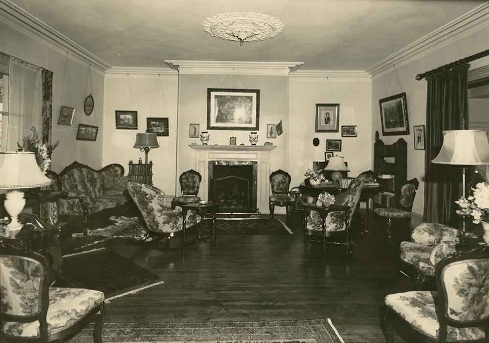Photo noir et blanc. Salon au décor surchargé. Des meubles sont disposés de chaque côté de la pièce avec au centre, un foyer.