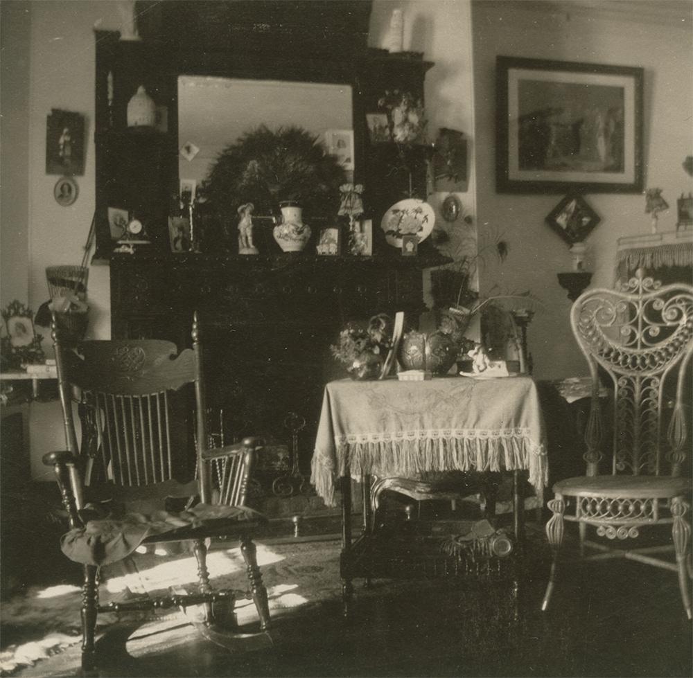 Photo noir et blanc d'un salon. Deux chaises et une table à l'avant-plan sont placées devant un foyer surmonté d'un grand miroir. De nombreux cadres ornent les murs et de nombreux objets décoratifs complètent la décoration de la pièce.