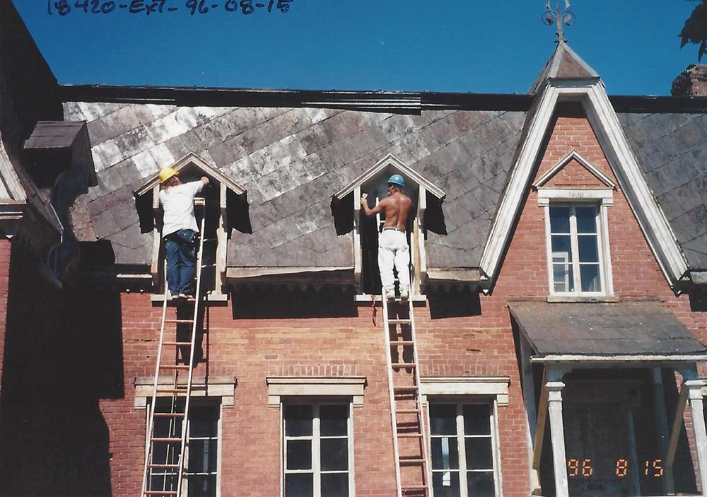 Photo couleur. Ouvriers dans des échelles qui réparent les lucarnes de la façade du Manoir.