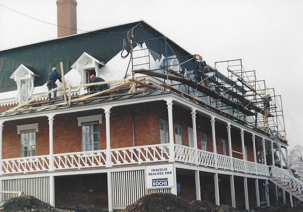 Photo couleur. Ouvriers travaillant à refaire la toiture du toit mansardé.