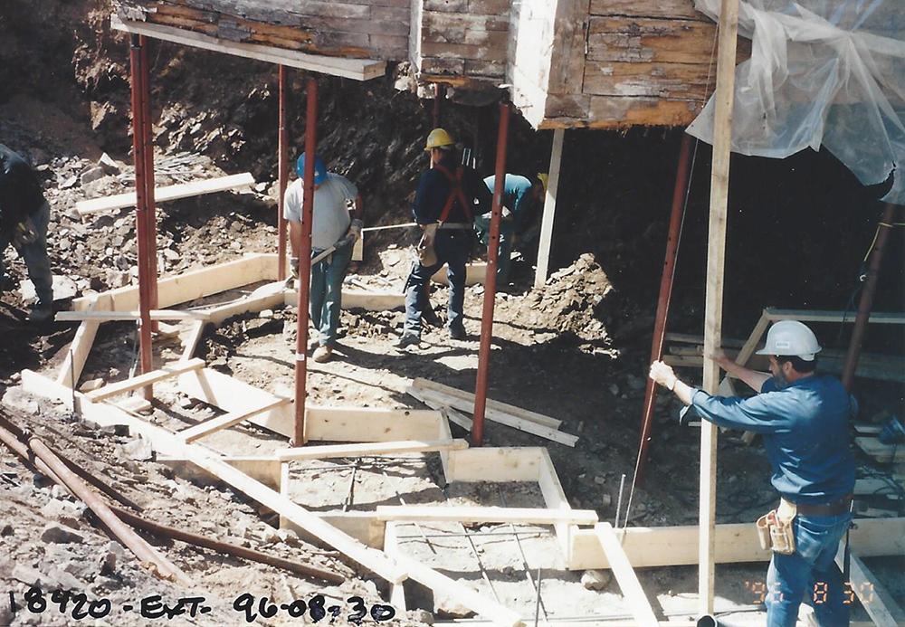 Photo couleur. Ouvriers qui préparent le coffrage des fondations du Manoir.