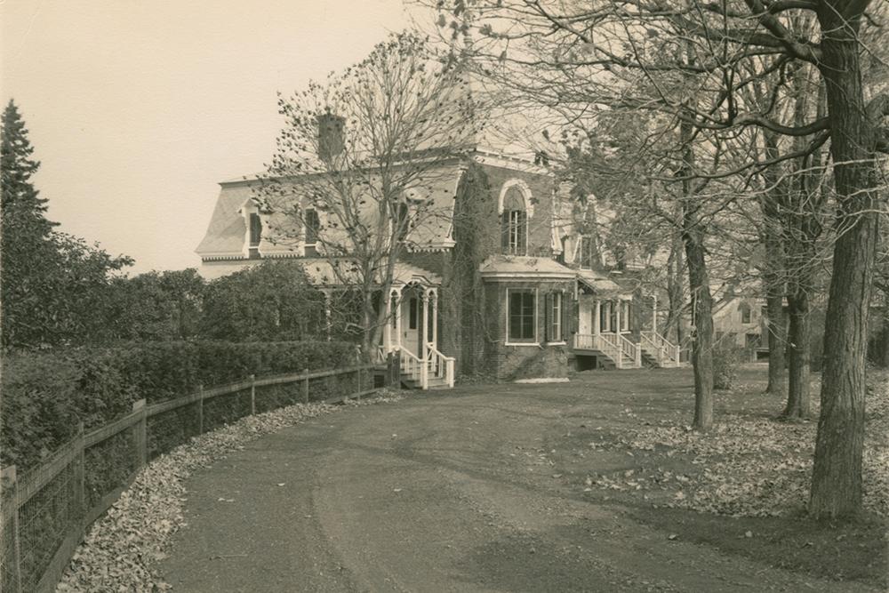 Photo noir et blanc. Un chemin à l'avant-plan mène à une maison entourée d'arbres en arrière-plan.