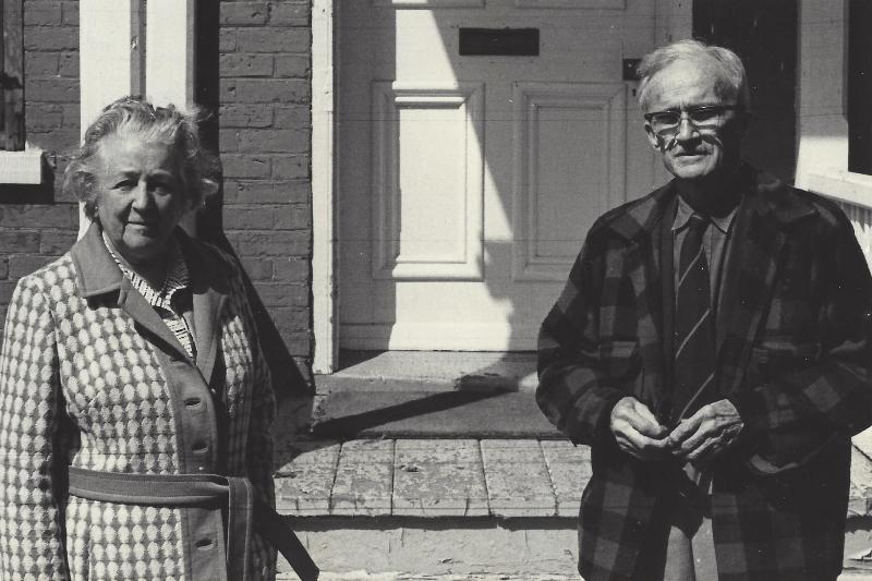 Photo noir et blanc. Deux personnes, une femme à gauche et un homme à droite prennent la pose à l'extérieur. À l'arrière, on devine la façade du Manoir Fraser.