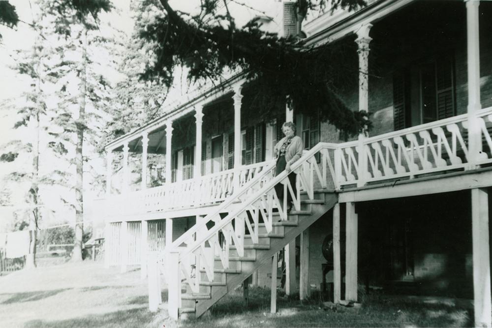 Photo noir et blanc. Femme âgée debout dans l'escalier extérieur qui donne sur la grande galerie entourant le manoir.