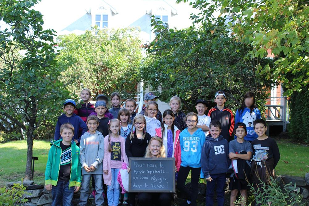 Photo couleur. Un groupe d'une vingtaine d'élèves prend la pose devant une maison. À l'avant-plan, l'enseignante tient un tableau sur lequel il est écrit «Pour nous, le manoir représente un voyage dans le temps!»