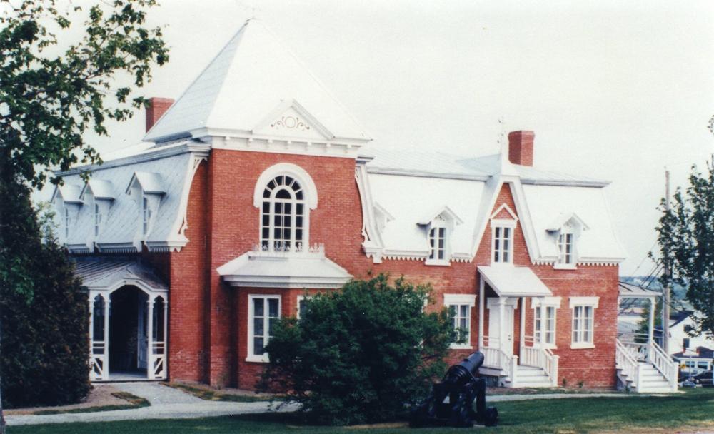 Photo couleur. Plan rapproché d'une maison de brique vue de façade.