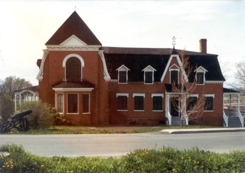 Photo couleur. Une maison inhabitée aux façades de briques , tous les volets des fenêtres sort fermés.