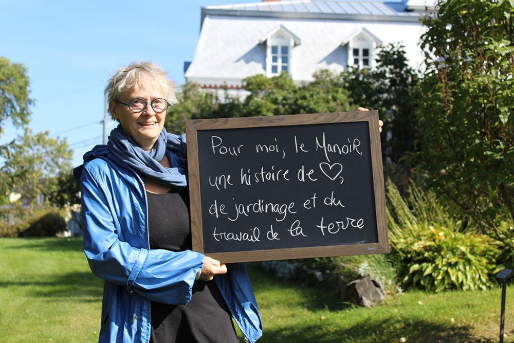 Photo couleur. Portrait d'une femme qui tient un tableau dans les mains. Une grande maison au toit mansardé est en arrière-plan.