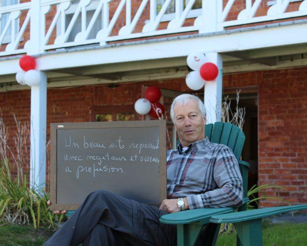 Photo couleur. Portrait d'un homme assis sur une chaise de jardin. En arrière plan, une maison de briques rouges.