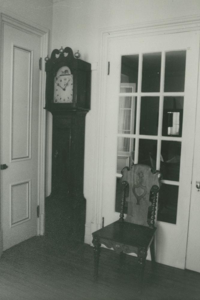 Photo noir et blanc. Une horloge adossée contre un mur et une chaise adossée contre une porte vitrée.