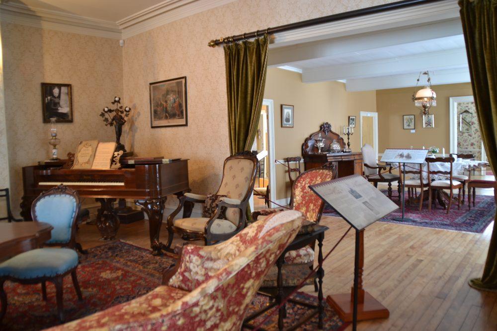 Photo couleur. Salon aménagé dans le style victorien, dans le coin un piano table, en arrière-plan une salle à manger, à l'avant-plan un panneau d'interprétation.