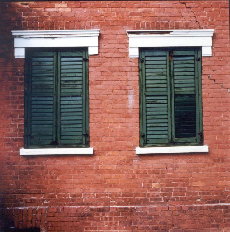 Photo couleur. Maison de briques avec des volets devant les fenêtres.