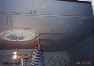 Photo couleur. Homme réparant le plafond du salon d'apparat du Manoir.