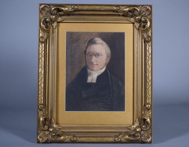 Portrait de William Abbott au fusain en couleur, adulte, tête et poitrine. Il a les cheveux courts et favoris châtain pâle, yeux gris pâle. Il porte un habit de ministre noir avec un collet blanc. Le fond est brun-gris foncé. Le portrait est placé dans un cadre au bois travaillé doré avec un passe-partout doré.