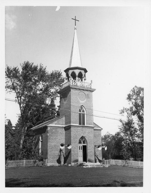 Photographie en noir et blanc de l'église Christ Church. L'église est en brique, la porte double, au centre, est ouverte d'un côté et surmontée d'une fenêtre en ogive. Une autre fenêtre de la même forme se trouve dans la tour du clocher. Les ouvertures du clocher sont en forme d'ogive et il est surmonté d'une longue flèche au bout de laquelle se trouve une croix noire. Deux haut-parleurs sont installés de chaque côté de la porte et beaucoup d'arbres se trouvent à l'arrière de l'église.