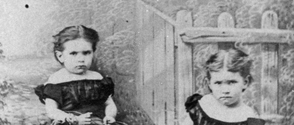 Photographie en noir et blanc de Maude et sa sœur Alice enfants. Elles sont assises au bord d'une clôture et regardent l'objectif avec un air sérieux. Elles portent des robes aux épaules dénudées et manches bouffantes foncées. Maude, à gauche, a les cheveux foncés, attachés à l'arrière de sa tête et porte une fleur à son bras droit. Alice, à droite, a les cheveux pâles, également attachés à l'arrière de sa tête. Elles sont assises derrière un arrangement de fleurs, deux chapeaux et trois roches sur la pelouse.