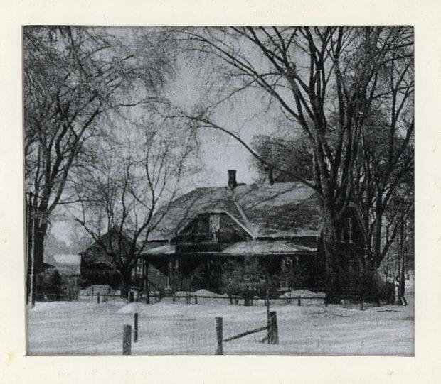 Photographie d'Elmbank, la résidence de Maude Abbott, en hiver, noir et blanc. Il s'agit d'une maison en briques de deux étages avec un toit à deux versants, deux cheminées et une galerie aux deux étages. On aperçoit une clôture en bois à l'avant de la maison, une affiche avec l'inscription « HONEY » devant celle-ci et beaucoup d'arbres sur le terrain.