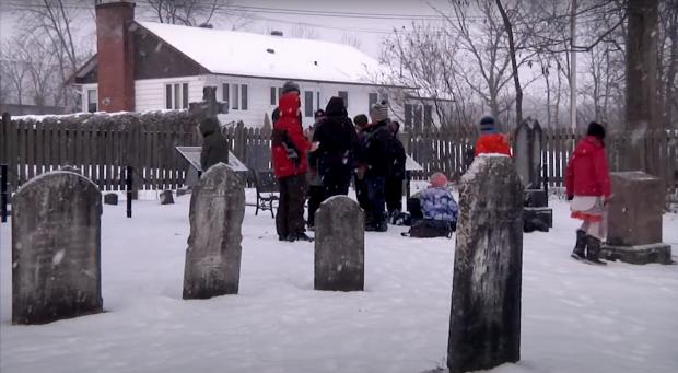 Groupe d'élèves dans un cimetière en hiver.